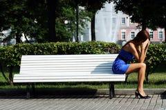 Traurige Frau, die auf Bank sitzt Stockbild
