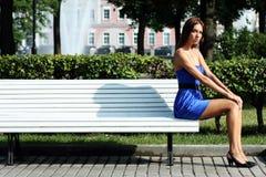 Traurige Frau, die auf Bank sitzt Stockfoto