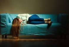 Traurige Frau, die auf Couch legt lizenzfreie stockfotografie