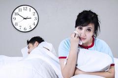Traurige Frau, die auf einem Bett sitzt Lizenzfreie Stockbilder