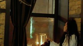 Traurige Frau, die auf einem Fensterbrett sitzt stock video footage