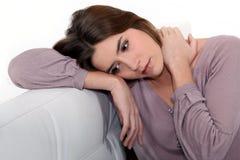 Traurige Frau, die auf einem Sofa sitzt Stockfotografie