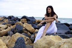 Traurige Frau, die auf Felsen vor Ozean sitzt Lizenzfreies Stockbild