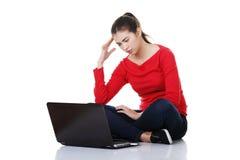 Traurige Frau, die auf Laptopbildschirm schaut. Stockbilder