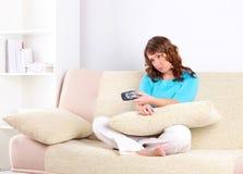 Traurige Frau, die auf Sofa mit Ferncontroller sitzt Stockfotografie