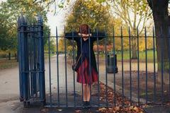 Traurige Frau, die auf Tor im Park sich lehnt Stockbilder