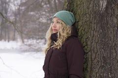 Traurige Frau, die am Baum im Winter sich lehnt Lizenzfreie Stockfotos