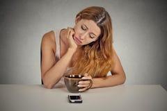 Traurige Frau, die bei Tisch sitzt, Handy betrachtend Stockbild