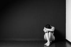Traurige Frau, die in der Ecke eines Raumes sitzt Lizenzfreies Stockbild