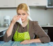 Traurige Frau, die an der Küche sitzt Stockbild