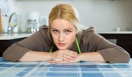 Traurige Frau, die an der Küche sitzt Lizenzfreie Stockfotografie