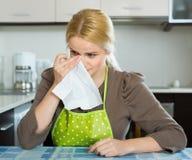 Traurige Frau, die an der Küche sitzt Stockfoto