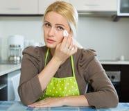 Traurige Frau, die an der Küche sitzt Lizenzfreies Stockfoto