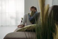 Traurige Frau, die ein Kissen umarmt Stockbilder