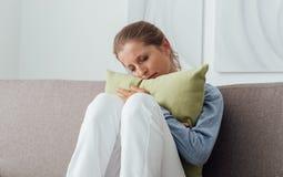 Traurige Frau, die ein Kissen umarmt Stockfoto