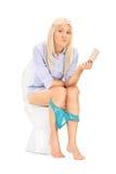 Traurige Frau, die eine leere Toilettenpapierrolle hält Stockfoto