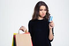 Traurige Frau, die Einkaufstaschen und Bank hält Stockfoto