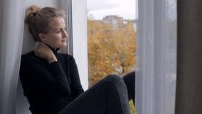 Traurige Frau, die Fenster betrachtet und auf Fensterbrett sitzt stock footage