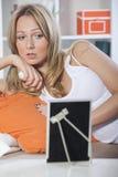Traurige Frau, die gestaltete Abbildung betrachtet Stockfotos