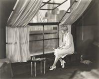 Traurige Frau, die heraus Fenster anstarrt lizenzfreie stockfotos