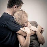 Traurige Frau, die ihren Ehemann umarmt lizenzfreies stockbild