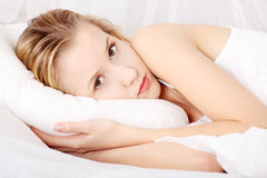 Traurige Frau, die im Bett liegt Lizenzfreies Stockbild