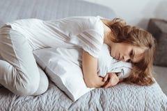 Traurige Frau, die im Bett liegt und ihr Kissen umfasst Stockbild