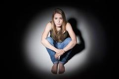 Traurige Frau, die im Pool des Lichtes sitzt Stockfotos