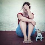 Traurige Frau, die mit einem kleinen Hund außer ihr schreit Lizenzfreies Stockfoto