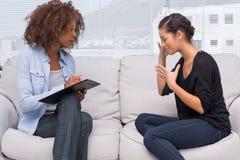 Traurige Frau, die mit ihrem Therapeuten spricht Stockbilder