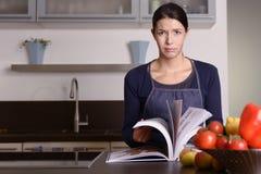 Traurige Frau, die Rezept-Buch an der Küche hält Stockfotos
