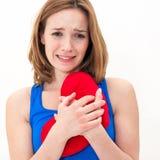 Traurige Frau, die rotes Valentinsgrußherz hält lizenzfreie stockfotos