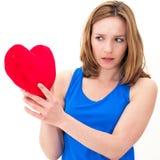 Traurige Frau, die rotes Valentinsgrußherz hält lizenzfreies stockfoto