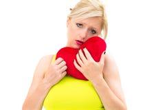 Traurige Frau, die rotes Valentinsgrußinneres anhält stockfotografie