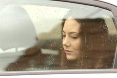 Traurige Frau, die unten durch ein Autofenster schaut Stockbilder