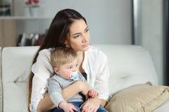 Traurige Frau, die weg mit ihrem Baby schaut Stockfotos