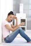Traurige Frau, die zu Hause auf Fußboden sitzt Stockbild
