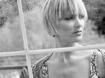 Traurige Frau am Fenster Stockfotos