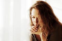 Traurige Frau gegen ein Fenster. Stockfoto