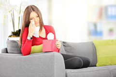 Traurige Frau gesetzt auf einem Sofa, das ihre Augen vom Schreien mit tis abwischt Stockbild