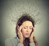 Traurige Frau mit besorgtem betontem Gesichtsausdruck und Gehirn, das in Linien Fragezeichen schmilzt Lizenzfreies Stockbild
