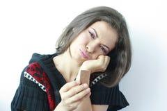 Traurige Frau mit einem Stück Schokolade in ihrer Hand Lizenzfreie Stockbilder