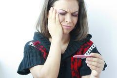 Traurige Frau mit einer Schwangerschaftprüfung in ihrer Hand lizenzfreie stockbilder