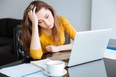 Traurige Frau mit Rechnungen und Laptop lizenzfreie stockfotos