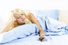 Traurige Frau mit Telefon im Bett Stockfotografie