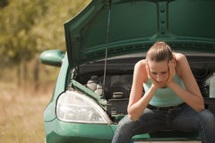 Traurige Frau mit unterbrochenem Auto Stockbild
