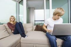 Traurige Frau neben dem Mann, der zu Hause Laptop im Wohnzimmer verwendet Lizenzfreie Stockbilder
