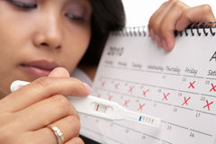 Traurige Frau, negative Schwangerschaftprüfung u. Kalender Lizenzfreie Stockfotos