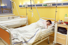 Traurige Frau von mittlerem Alter, die im Krankenhaus liegt Lizenzfreie Stockfotografie