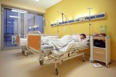 Traurige Frau von mittlerem Alter, die im Krankenhaus liegt Lizenzfreie Stockfotos